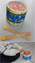 Hudební nástroje_bubínek (základ=krabička od tavených sýrů; čtvrtka na obvod a horní část, na vybarvení použity gelové voskovky zn.Staedtler; paličky = dřívka :)