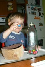 Druhá aktivita měla být první práce s kleštičkama na cukr. Ale to ne-e. Všechny věci do láhve naházel rukou - něco bylo lehké něco zvonilo. Taky zábava. Pak tam málem skončily i ty kleštičky :-D.
