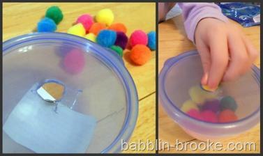 trénink motoriky - vhazování bambulek. Je-li více mističek, lze to třídit podle barev.