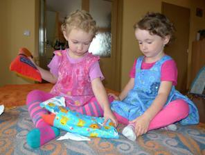 Anička pomáhá rozbalovat dárek Denisce, která slaví třetí narozeniny