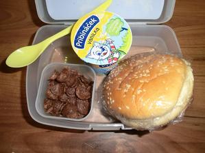 Hamburgerová bulka s máslem a medem, čokoládové lupínky a malý Pribináček